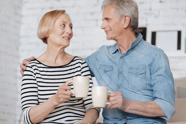 Горячие чувства. два пожилых харизматичных человека проводят время вместе, сидя на кровати и болтая с чашками в руках