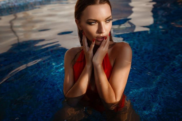 Hot female in stylish swimsuit. outdoor fashion portrait of glamour lady enjoying her vacation on luxury villa in hot tropical island.