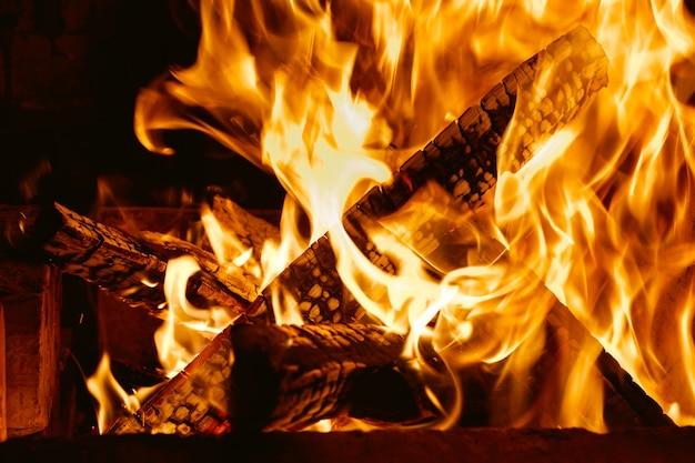 乾いた薪でいっぱいの熱い暖炉、暖かい燃える火。
