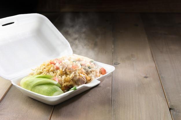 Hot food in foam box on wood table