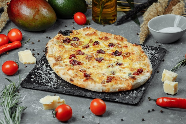 Горячие четыре сыра вкусная деревенская домашняя американская пицца с толстой корочкой на черном столе.