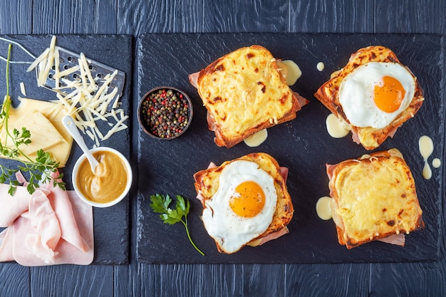 Hot french toasts croque monsieur and croque madame with slices of boiled ham, melted emmental cheese and fried sunny side up egg on a stone tray with ingredients on a wooden table, view from above