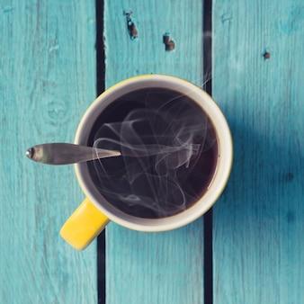 Горячий свежий кофе или чай на яркой деревянной стене. плоская планировка.