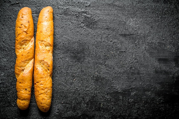 Hot fresh french baguette. on black rustic