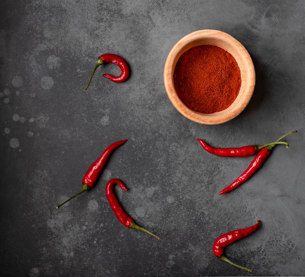 Hot fresh pepper and pepper powder on a dark background. top view