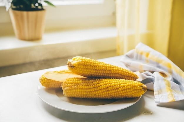 갓 요리한 뜨거운 옥수수 속대와 식탁에 있는 접시에 증기가 있습니다. 채식주의 자 음식