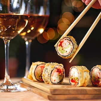 연어와 와인을 곁들인 뜨거운 튀김 스시 롤. 스시 메뉴. 일본 음식. 뜨거운 튀긴 스시 롤