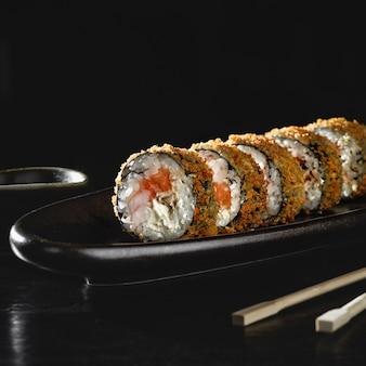 연어와 함께 뜨거운 튀긴 스시 롤. 스시 메뉴. 일본 음식. 검은 표면에 뜨거운 튀긴 된 스시 롤