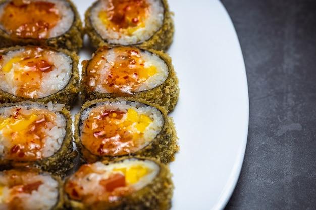 Горячий жареный суши-ролл с лососем. суши-меню. японская еда. горячие жареные суши-роллы на белой тарелке. крупный план