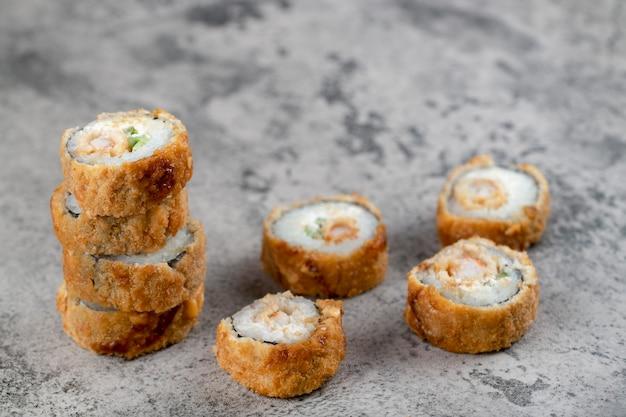 Горячие жареные суши-роллы на каменном фоне.