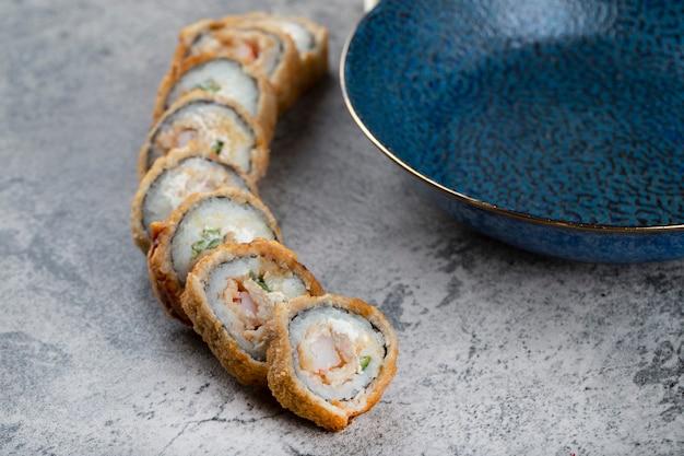 Горячие жареные суши-роллы с пустой тарелкой на каменном столе.