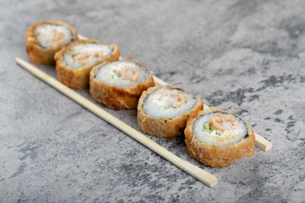 Горячие жареные суши-роллы с деревянными одноразовыми палочками на каменном столе.
