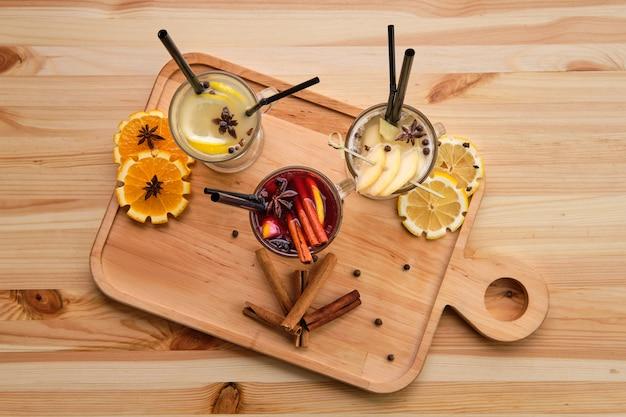 Горячие фруктовые напитки - малина с апельсином, лайм с имбирем и груша с лаймовым чаем, вид сверху