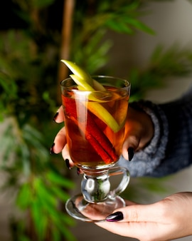 Hot fruit tea with apple and cinnamon in a glass
