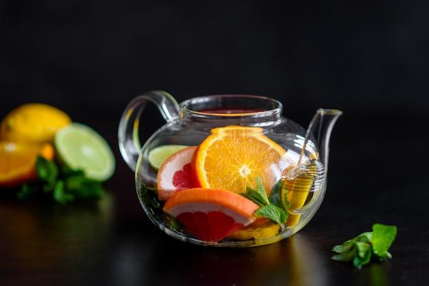 Hot fruit tea with lemon, mint, orange, lime and grapefruit in a beautiful glass teapot