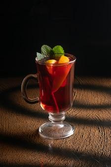 Горячий фруктовый чай с апельсином, дольками апельсина, листьями мяты и палочкой корицы в прозрачном стеклянном стакане с ручкой.