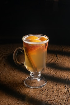 Hot fruit tea with orange slices, cloves and cinnamon sticks in a clear glass glass with a handle.