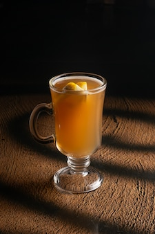 Hot fruit tea with orange slices and honey in a clear glass glass with a handle.