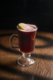 Горячий фруктовый чай с малиновым вареньем и дольками яблока в прозрачном стеклянном стакане с ручкой.