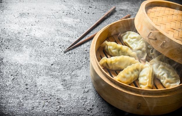 Hot gedza dumplings in a bamboo steamer on black rustic table