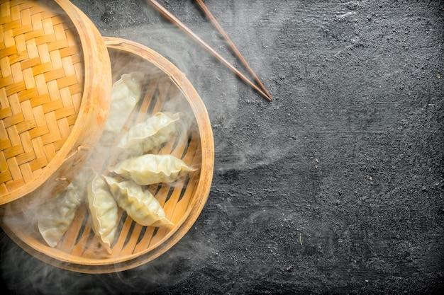 Горячие пельмени гедза в бамбуковой пароварке.