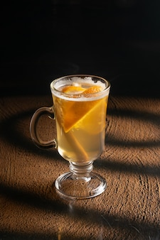 Hot ginger tea with orange slices and a stick of cinnamon in a clear glass glass with a handle.