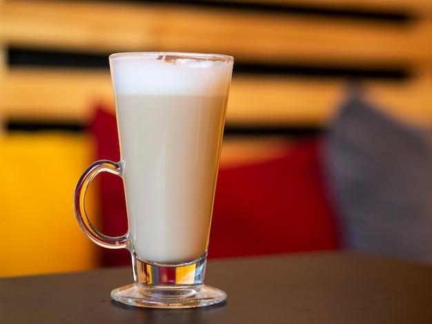 Горячая стеклянная чашка кофе латте на деревянном столе в уютном теплом интерьере