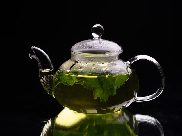Hot glass teapot on a black background green mint tea herbal tea and healthy drink concept