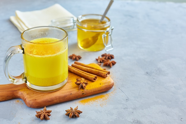 Hot golden milk with turmeric powder in glasses