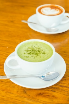Hot green matcha latte in white cup