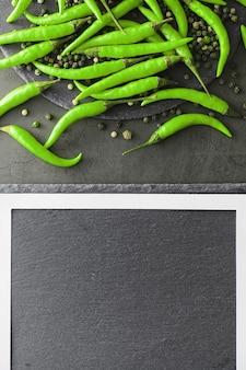 Острый зеленый перец. чилийский перец на черном фоне.