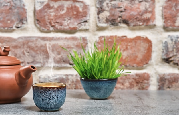 Hot green tea in a blue bowl, selective focus, steam rises above the cup, next to a clay teapot. gray stone table, brick vintage wall. close-up, tea ceremony, minimalism, place for text