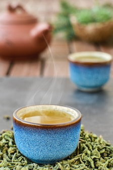 Hot green tea in a blue tea bowl, stone table. steam rises from the bowl. tea leaves next to the cup. close-up, tea ceremony. minimal