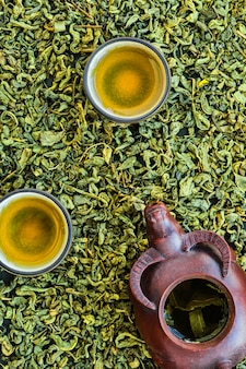 Hot green tea in cups, ceramic teapot on a stone table, layout. fermented tea leaves are scattered on the table. view from above. minimal