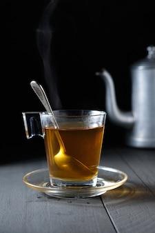 Горячий зеленый чай дымится в стеклянной чашке и черном фоне