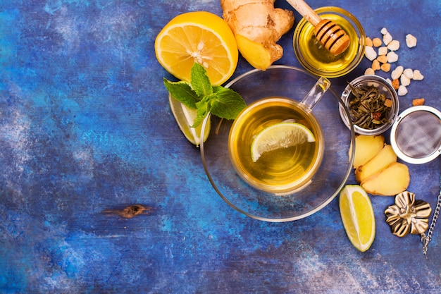 Hot green tea in a glass cup served with lemon, ginger, lime, honey and mint on grunge blue wooden background. top view.