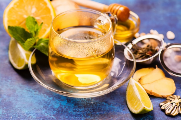 Hot green tea in a glass cup served with lemon, ginger, lime, honey and mint