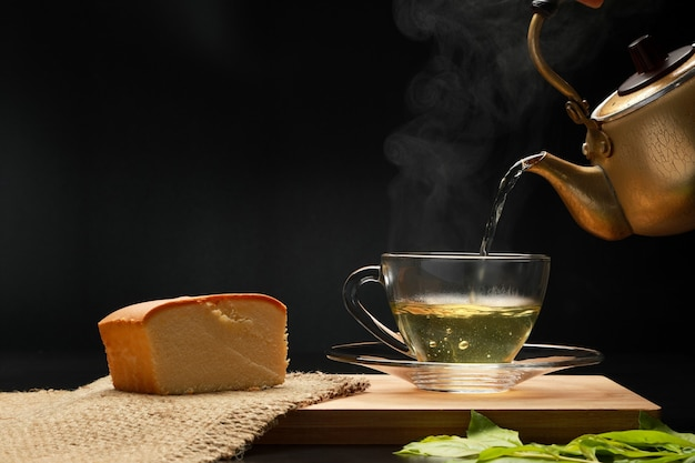 The hot green tea in the glass cup with pouring from the golden teapots with smoke