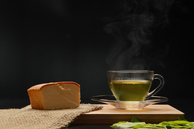 The hot green tea in the glass cup with smoke and butter cake on the wooden board.