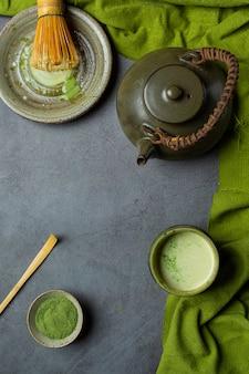 Tè verde caldo in un bicchiere con crema condita con tè verde, decorato con tè verde in polvere.