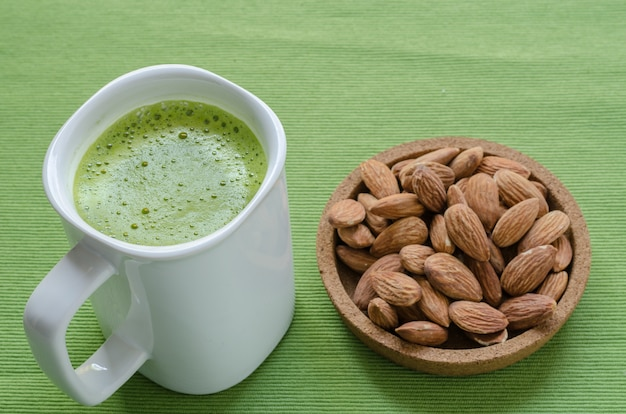 Hot green tea latte in lazy time with almonds nut