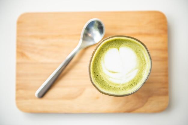 Горячий зеленый чай латте с ложкой на деревянной тарелке