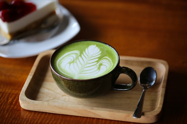 Hot green tea matcha latte in cup on table.