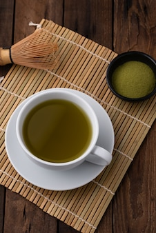 Hot green tea with powder on wood