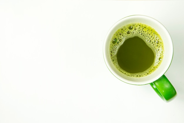 Hot greentea in cup on white background. top view.