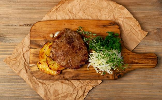 Горячий стейк из говядины чивас на гриле с салатом из капусты, жареным картофелем и зеленью на деревянной разделочной доске. хорошо прожаренный бифштекс или антрекот барбекю в деревенском стиле