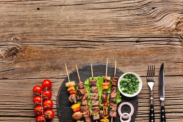Hot grilled kebab skewers with vegetable on black slate over wooden surface