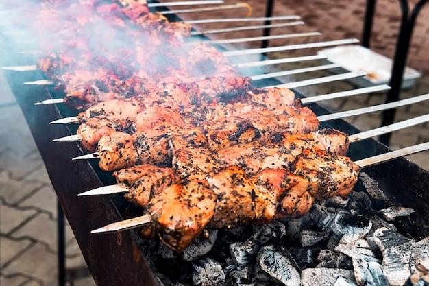Горячий кебаб из свинины на гриле или кебаб барбекю на фоне древесного угля с травами и специями заделывают. фото кубики свинины на гриле, украшенные острым перцем