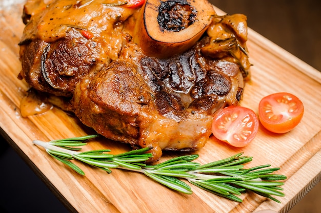 Hot grilled spare ribs with fresh tomatoes on an wooden cutting board