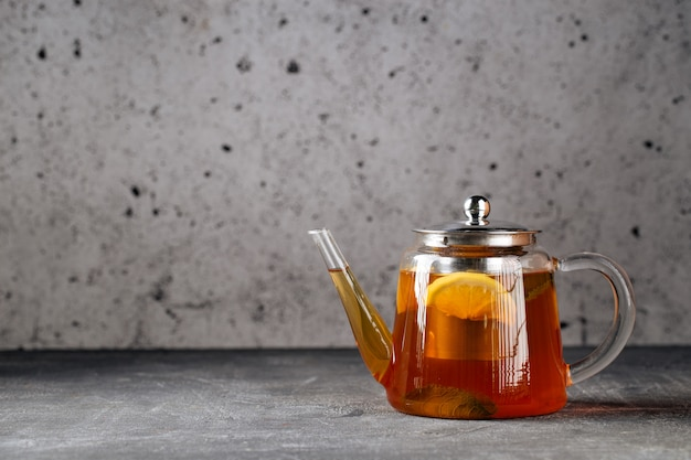 Горячий полезный черный чай с лимоном в стеклянном чайнике